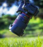 Professional SLR camera hanging in the air over green juicy fresh grass royalty free stock photo