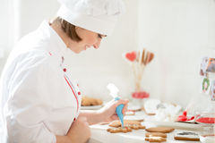 Professional smiling confectioner decorating a gingerman Stock Photo