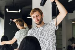 Professional smiling male stylist blow drying woman`s hair with a dryer in salon stock images