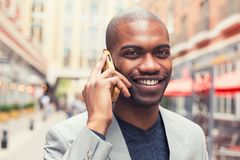 Professional smiling man using smart phone talking on mobile. Portrait young urban professional smiling man using smart phone talking on mobile outside outdoors Royalty Free Stock Photos