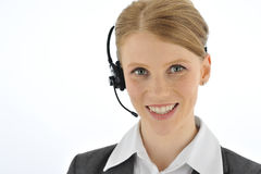Professional smiling telephone operator. Red haired woman with powerful posture. Her eyes are in focus Royalty Free Stock Photography