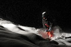 Professional snowboarder dressed in the orange sportswear riding. With the snowboard at the dark snowy night stock images