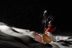 Professional snowboarder riding down a snowy hill at night. Professional snowboarder in black and orange sportswear riding down a snowy powder hill at black royalty free stock photography