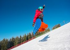 Professional snowboarder riding in the mountains Stock Photography