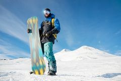 A professional snowboarder stands with his snowboard royalty free stock image