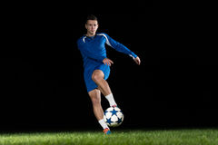 Professional Soccer Player Kicking Ball Isolated On Black Royalty Free Stock Photos