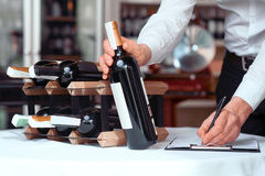 Professional sommelier being involved in work. Everything in order. Professional sommelier holding wine bottle and putting it on the table while making notes Royalty Free Stock Images