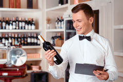 Professional sommelier being involved in work. Like my job. Cheerful positive handsome sommelier holding folder and wine bottle while being involved in work Royalty Free Stock Photos