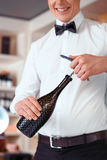 Professional sommelier opening bottle of wine. Pleasant handsome professional sommelier holding opener and opening bottle of wine while expressing joy stock images