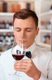 Professional sommelier tasting wine. Gorgeous aroma. Portrait of pleasant professional sommelier holding wine glass and tasting it while closing his eyes Royalty Free Stock Image
