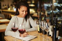 Professional sommelier at work. Attractive mixed race woman sitting at restaurant table, tasting different kinds of red wine and writing data on paper Royalty Free Stock Photography