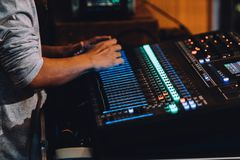 Professional soundboard including audio mixer control panel with buttons and sliders, cords and microphone in recording studio. Professional soundboard stock image