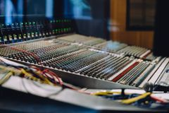 Professional soundboard including audio mixer control panel with buttons and sliders, cords and microphone in recording studio.  stock images