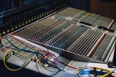 Professional soundboard including audio mixer control panel with buttons and sliders, cords and microphone in recording studio.  stock photo