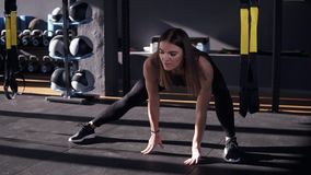 Professional in sport. Front view of beautiful young woman in sportswear doing stretching while on the floor in a dark stock video