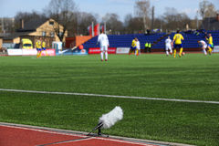 Professional sport microphone. On a football field with windshield for live sport broadcasting Stock Photos