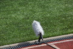Professional sport microphone. On a football field with windshield for live sport broadcasting Royalty Free Stock Images