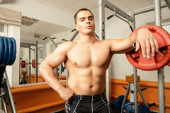 Professional sports. Handsome muscular man with weight training equipment in a gym. Sports, bodybuilding. Healthy lifestyle Stock Photography