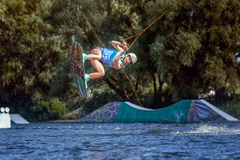 Professional sportswoman goes wakeboard ride. Professional athlete skates on a wakeboard, she trains to do tricks in a jump Royalty Free Stock Photography