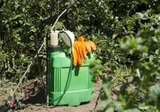 Professional spray pump and other tools in the garden. Seasonal spraying tomatoe plants, trees on the farm. Closeup of spray pump, protective gloves, respirator royalty free stock photography
