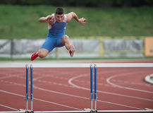 Professional sprinter jumping. Over a hurdle on a running track Royalty Free Stock Photos
