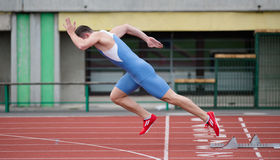 Professional sprinter's explosive start. On the running track. Side view Stock Image
