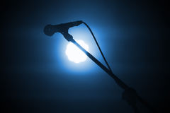 Professional stage microphone in light. Professional stage microphone in bright spot light over dark blue background Stock Images