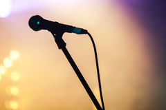 Professional stage microphone silhouette. Professional stage microphone over blurred colorful background Stock Image