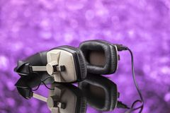 Professional stereo headphones on violet background out of focus Stock Photos