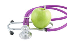 Professional stethoscope and green apple Stock Photos
