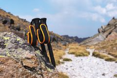 Professional sticks for climbing a mountain near a stone on a high mountain path against a blue sky and white clouds. The concept of active recreation and Royalty Free Stock Image