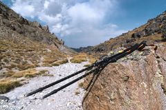 Professional sticks for climbing a mountain near a stone on a high mountain path against a blue sky and white clouds. The concept of active recreation and Royalty Free Stock Images