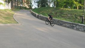 Professional strong skinny cyclist pedaling hard towards hill as a part of his training. Professional strong skinny cyclist pedaling hard towards hill as a part stock footage