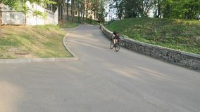 Professional strong skinny cyclist pedaling hard towards hill as a part of his training. Slow motion.  stock video