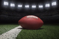 Professional style football on field with stripe under stadium l Stock Image