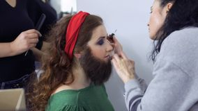 Stylists sticks artificial beard on girl`s face, dressing room in theatre. Professional stylist creates a scenic character for young actress. She sticks the stock video footage
