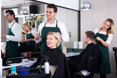 Professional stylist cutting hair of elderly blonde Stock Photography
