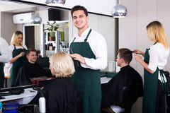 Professional stylist cutting hair of elderly blonde Royalty Free Stock Photos