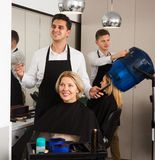 Professional stylist cutting hair of elderly blonde in salon. Professional stylist cutting hair of elderly blonde in hairdressing salon royalty free stock photography