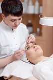 Professional stylist making eyelash extension for women Royalty Free Stock Photography