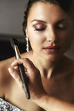 Professional stylist putting on makeup on beautiful brunette bri Royalty Free Stock Photography