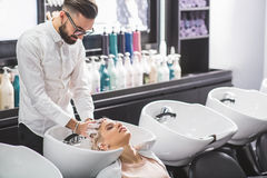 Professional stylist is working with a client. Concentrated hairdresser is washing female hair. He is applying shampoo Stock Photo