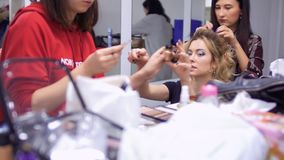 Professional stylists creates a scenic character for actress in theatre. Professional make-up artist makes a beautiful greasepaint to the actress in theatre. The stock video footage