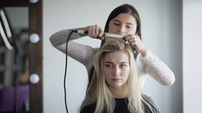 Professional stylists working on a new and fashionable shape for its rich client. Blonde in an expensive beauty salon is stock footage