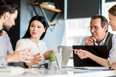 Professional successful team sitting around table stock photo