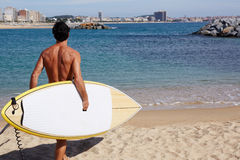 Professional surf rider began his surf session. Rear view attractive man with sexy body going to the sea holding big copy space surfing board, handsome man Royalty Free Stock Photos