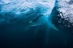 Professional surfer with surfboard dive underwater with big ocean wave. royalty free stock photo
