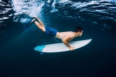 Professional surfer with surfboard dive underwater with ocean wave. royalty free stock photos