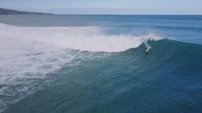 Professional surfer surfing in big white foamy splashing wave in blue turquiose ocean water in 4k aerial summer seascape stock video