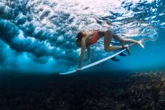Professional surfer woman with surfboard make duck dive underwater with ocean wave. stock photo
